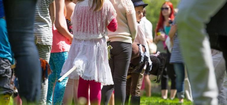 Lapset ratsastamassa keppihevosilla.